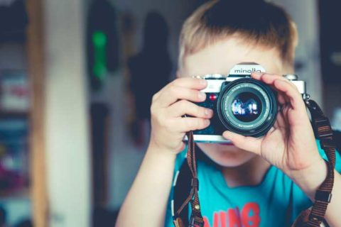 Little boy taking pictures with camera